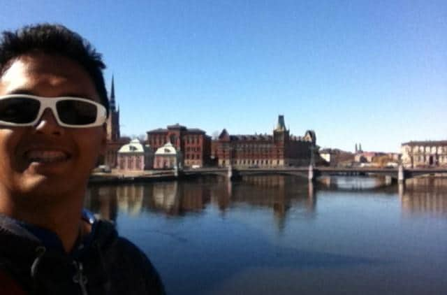 Eurail customer testimonials | Man smiling with the European architectures and a bridge in the background
