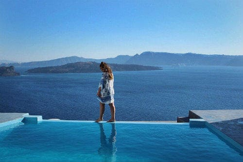 Everything about Eurail | Girl walking on the side of swimming pool iin santorini, Greece
