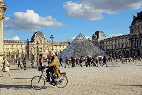 Everything about Eurail | Old man on the bicycle passing by the Louvre museum in Paris, France