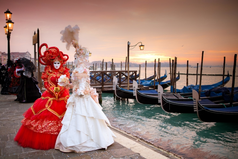 Masked women in Venice at sunset