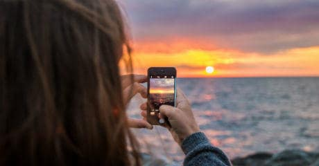 why_eurail_is_your_greenest_choice_-_female_taking_a_photo_of_sunset_with_mobile_at_vang_hasle_in_denmark